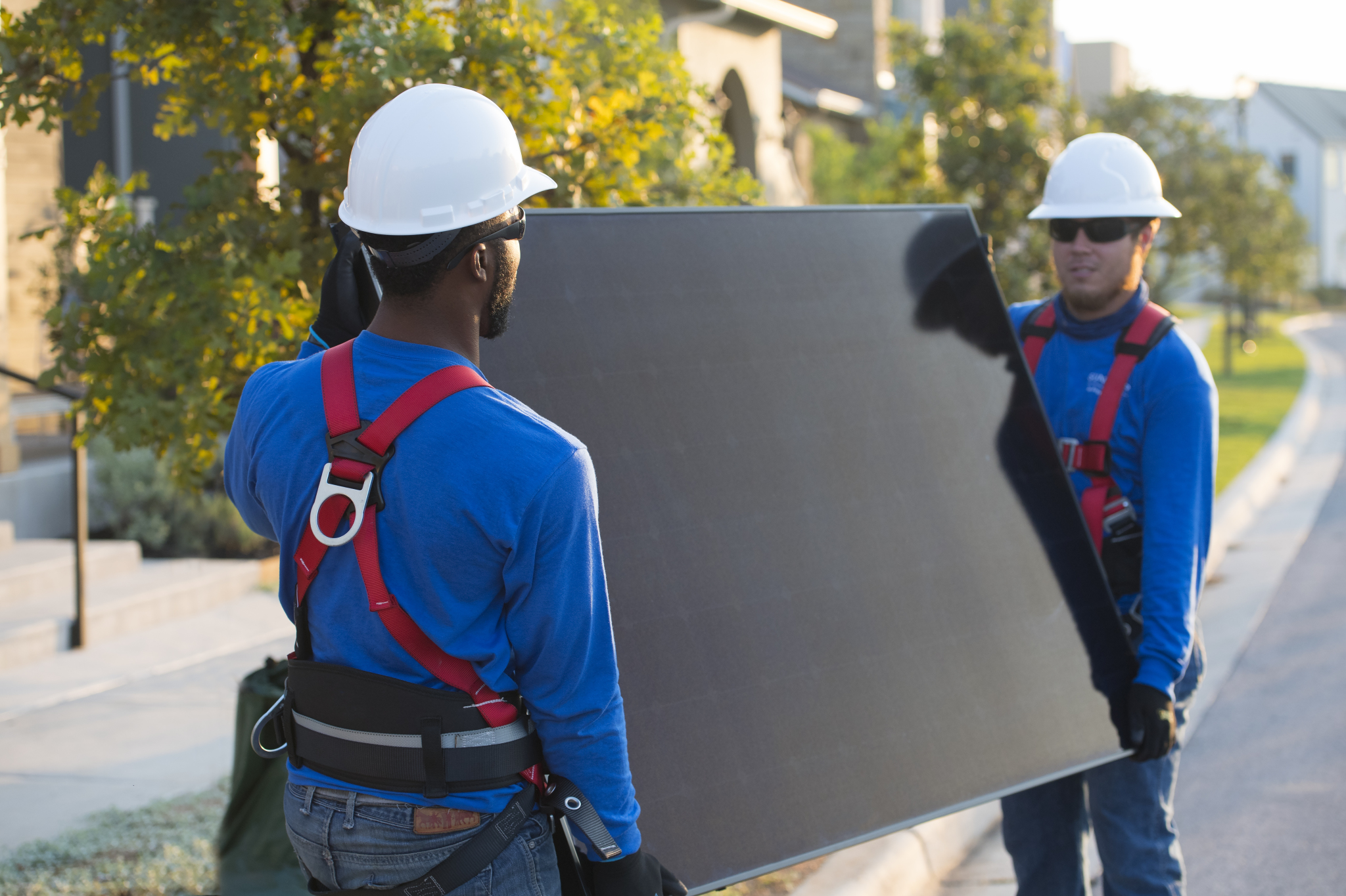 men carrying solar panel