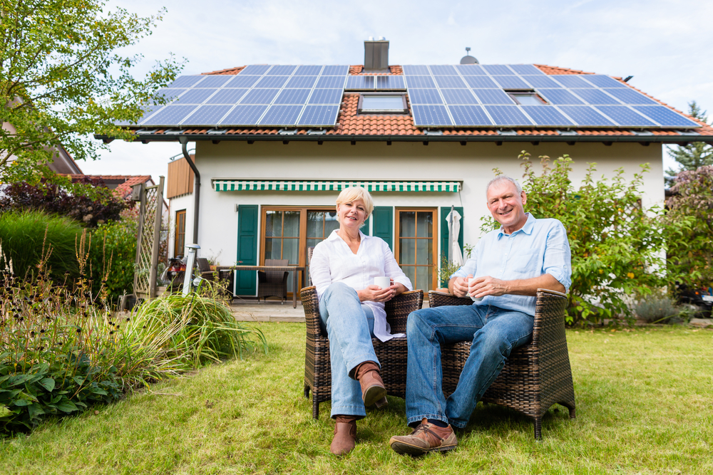 Couple posing in front of solar home