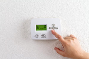 Hand lowers temperature on thermostat